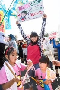 手作りのポスターを持つ城間さんと2人の娘