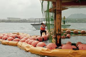 ボーリング基地の付近でいきなり海に飛び込んだ活動家は、ネットを伝って登り始めた。