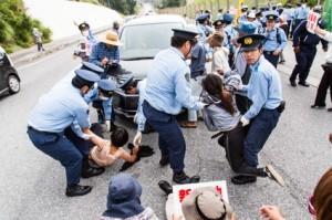 キャンプ・シュワブのゲート前で海上保安庁の職員が乗った車の進入を阻止しようとする市民。警官隊の強引な排除によってけが人が続出している。