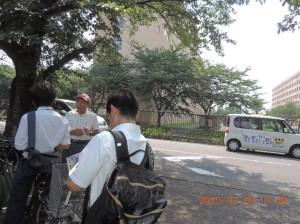 写真中央の自衛隊隊舎では数年前19才の自衛官が飛び降り自殺した。宣伝カーの 向こうに訴える区議、その前方の自転車置き場で隠れながら聞く隊員た ち。隊舎に入る一人の自衛官の姿が見える。