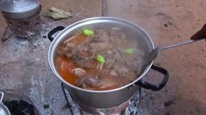 ぶつ切りにされた獣肉の煮込み;緑色のものはトウガラシ©西原恵美子