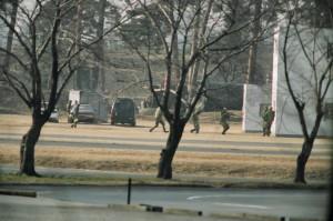 市街地戦闘訓練の写真。朝霞駐屯地:2004年イラク派遣直前の海道の部隊の演習。敵に拘束されている仲間の自衛官を四人一組であらゆる方向 に銃を向け ながらドアを蹴破り救出する状況。イラク復興行動史には、徹底した訓練して 「危ないと思ったら撃て」と指導。