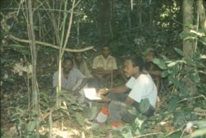 森の中で先住民ガイドと調査研究を実施中の青年(手前)©西原智昭