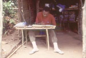 森の中のキャンプ地での臨時テーブルでデータ整理をするコンゴ人研修者©西原智昭
