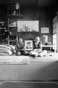 福島第一原発で事故死した息子の遺影を持つ両親 = 新潟県五泉市