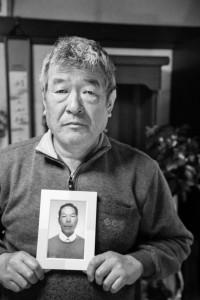 自殺した男性の遺影を持つ兄 = 神奈川県小田原市